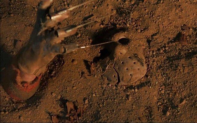 Foto de la escena de la película donde la mano de Freddy Krueger cogiendo la máscara de Jason Voorhees